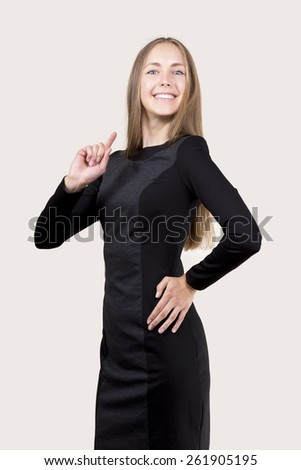 smiling young woman in black dress showing her forefinger up - stock photo