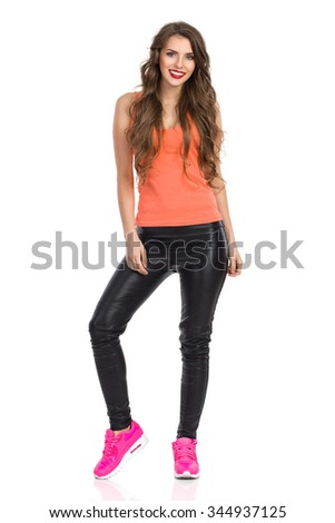 Smiling young woman in black leather trousers, orange shirt and pink sneakers standing and looking at camera. Full length studio shot isolated on white.