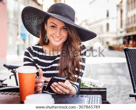 Smiling young woman in black shirt with white stripes and big black summer hat sitting at the table in summer cafe. - stock photo
