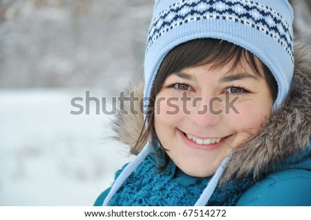 smiling young woman in blue coat outdoors - stock photo