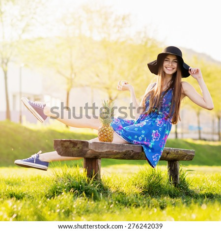Smiling young woman in blue floral dress, fedora and canvas shoes sitting in park on sunny summer day. Portrait of bohemian teenage girl with pineapple. Natural light, retouched, square format. - stock photo