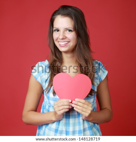 Smiling young woman in casual clothes holding red heart symbol of love and Valentine's Day - stock photo
