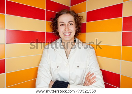 Smiling young woman in colorful tiled corner - stock photo