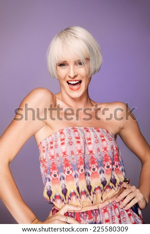 Smiling young woman in front of purple background - stock photo