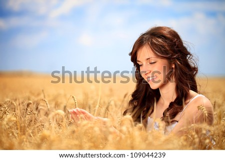 Smiling young woman in golden wheat take care of the wheat