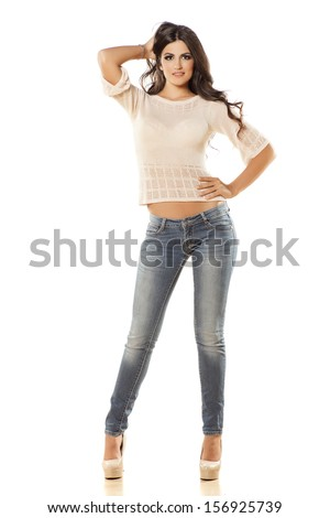 smiling young woman in jeans and blouse posing on white background - stock photo