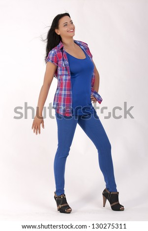 Smiling young woman in jeans in the  the office and checked blouse with blue top / Style News - stock photo