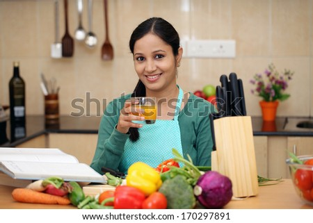 Smiling young woman in kitchen  - stock photo