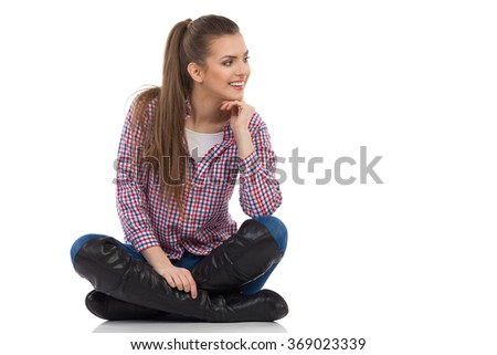 Smiling young woman in lumberjack shirt, jeans and black boots sitting on a floor with legs crossed and looking away. Full length studio shot isolated on white. - stock photo