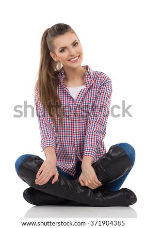 Smiling young woman in lumberjack shirt, jeans and black boots sitting on a floor with legs crossed and looking at camera. Full length studio shot isolated on white. - stock photo