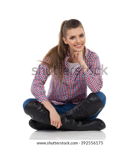 Smiling young woman in lumberjack shirt, jeans and black boots sitting on a floor with legs crossed holding hand on chin and looking at camera. Full length studio shot isolated on white. - stock photo