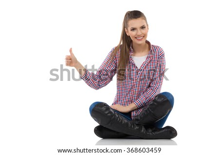 Smiling young woman in lumberjack shirt, jeans and boots sitting on a floor with legs crossed and showing thumb up. Full length studio shot isolated on white. - stock photo