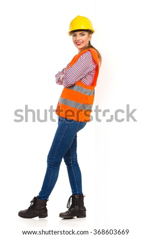Smiling young woman in orange reflective vest, lumberjack shirt, jeans and black boots, standing with arms crossed and leans on a white wall. Full length studio shot isolated on white. - stock photo