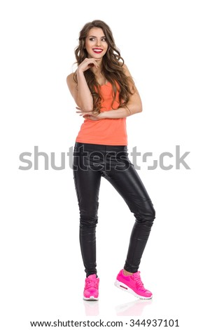 Smiling young woman in orange shirt, black leather trousers and pink sneakers standing, holding hand on chin and looking away. Full length studio shot isolated on white. - stock photo