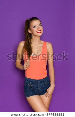 Smiling young woman in orange shirt posing and holding her ponytail in hand. Three quarter length studio shot on purple background. - stock photo