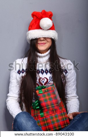 Smiling young woman in red christmass hat at grey background