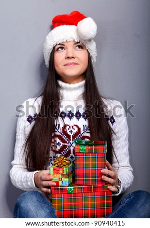 Smiling young woman in red christmass hat at grey background - stock photo