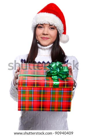 Smiling young woman in red christmass hat at white background with gifts - stock photo