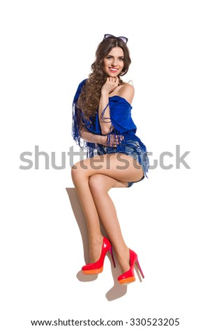 Smiling young woman in red high heels sitting at the white banner with legs crossed at knee holding hand on chin and looking at camera. Full length studio shot isolated on white. - stock photo