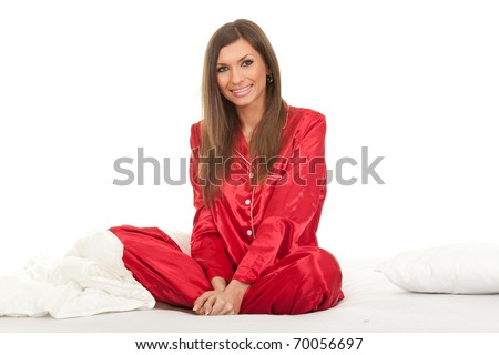 smiling young woman in red pajamas in white bedding sitting with crossed legs - stock photo