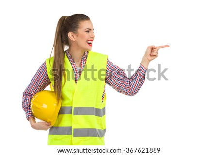 Smiling young woman in reflective vest holding hardhat under her arm looking away and pointing. Waist up studio shot isolated on white. - stock photo