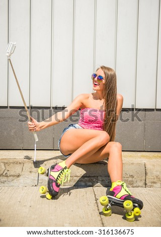 Smiling young woman in rollers is making selfie photo with selfie stick.