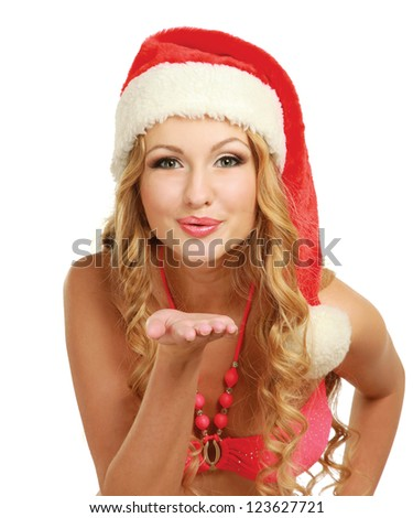 Smiling young woman in Santa hat blowing air kiss, isolated on white background