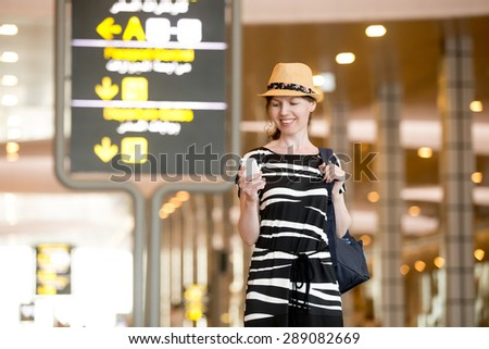 Smiling young woman in straw hat in her 20s waiting for flight in modern airport terminal building, holding mobile phone, looking at screen, using cellphone app or messaging - stock photo