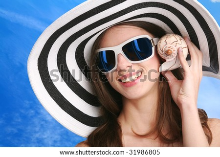 smiling young woman in striped hat and black sunglasses listens seashell - stock photo