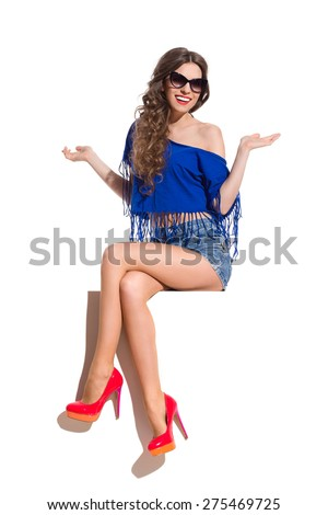 Smiling young woman in sunglasses, blue top, jeans shorts and red high heels sitting at the white banner with legs crossed at knee and arms outstretched. Full length studio shot isolated on white. - stock photo