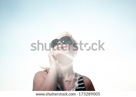 Smiling young woman in sunglasses talking on the phone and sun shines behind her back - stock photo