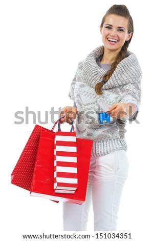 Smiling young woman in sweater with christmas shopping bag giving credit card