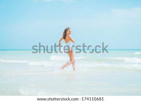 Smiling young woman in swimsuit running into sea