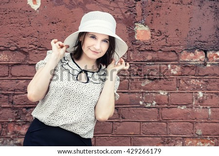 Smiling young woman in white hat posing against brick wall background. Girl holds the edges of the hat by hands. Toned photo with copy space. Vintage style photo. - stock photo
