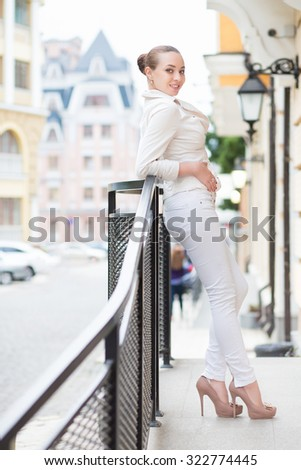 Smiling young woman in white pants and jacket posing outdoors - stock photo