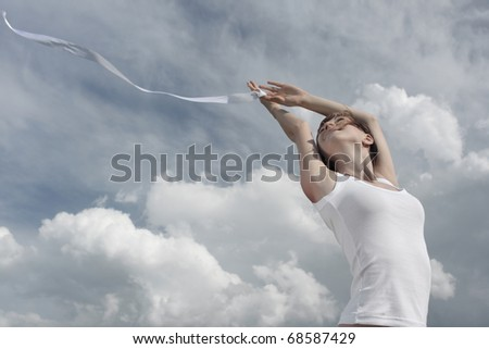 Smiling young woman in white shirt with white ribbon on cloudy sky background - stock photo