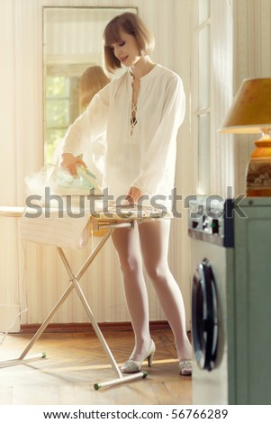 Smiling young woman in white stockings steaming the skirt on the ironing board - stock photo