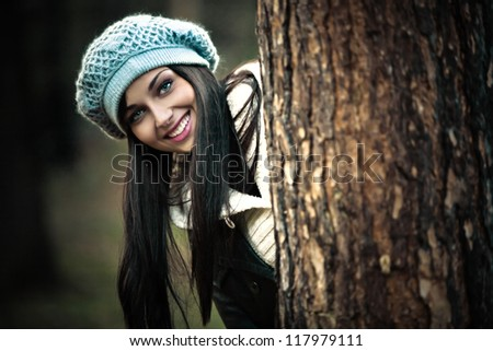smiling young woman in winter clothes outdoor portrait behind the tree - stock photo