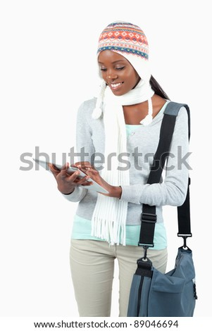 Smiling young woman in winter clothes using her tablet against a white background - stock photo