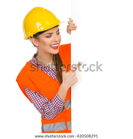 Smiling young woman in yellow hardhat, orange reflective vest and lumberjack shirt standing behind big white banner and pointing. Waist up studio shot isolated on white. - stock photo