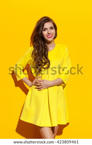 Smiling young woman in yellow mini dress posing with hand on hip and looking at camera. Three quarter length studio shot on yellow background. - stock photo