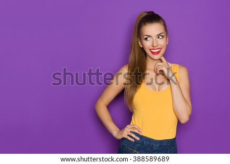 Smiling young woman in yellow shirt posing with hand on hip and looking away at copy space.Waist up studio shot on purple background. - stock photo
