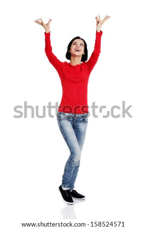 Smiling young woman  is holding something abstract above her head. Happy girl with raised hands. Isolated on white background.