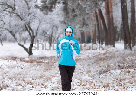 Smiling young woman jogging at winter park. Outdoor sport healthy running - stock photo