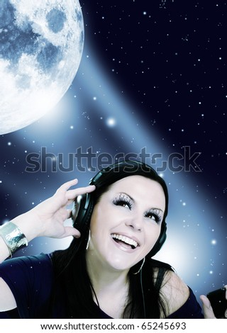 smiling young woman listening music in the moon light - stock photo