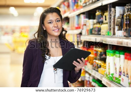 Smiling young woman looking at camera while holding digital tablet in shopping centre - stock photo