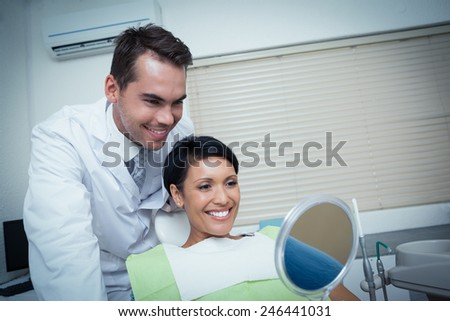 Smiling young woman looking at mirror in the dentists chair - stock photo