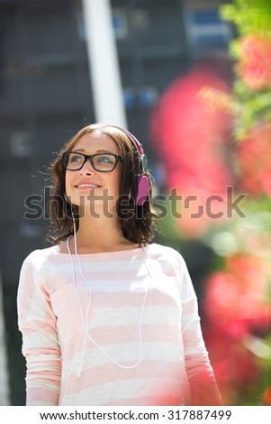Smiling young woman looking away while listening music on sunny day - stock photo