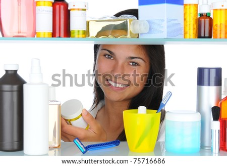 Smiling young woman looking in bathroom medicine cabinet. Horizontal format isolated on white, Focus is on the person.