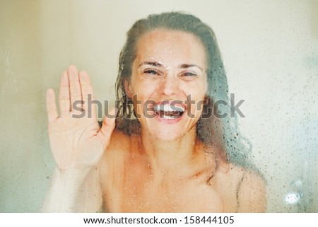 Smiling young woman looking through weeping glass in shower - stock photo